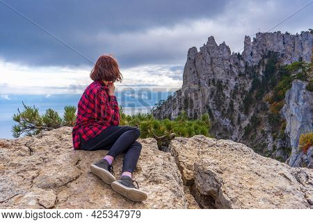 Rear View Of Young Woman Sitting On Mountain Cliff Stones And Admiring Beautiful Landscape Of Mounta