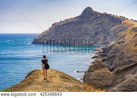 Rear View Of Young Woman Standing On Mountainous Road And Admiring Beautiful Landscape Of Sea And Mo