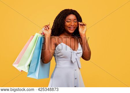 Seasonal Sales And Shopping. Young Black Woman Carrying Bright Shopper Bags With Purchases, Orange B