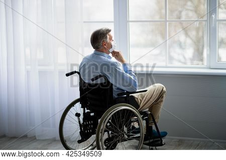 Handicapped Old Man In Wheelchair Wearing Face Mask, Suffering From Loneliness In Retirement Home Du