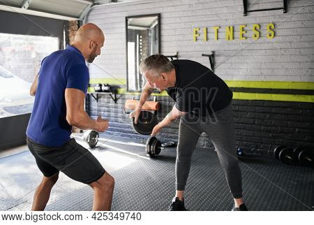 Male Personal Trainer Motivating And Supporting Elderly Senior Man While Doing Wood Choppers Dynamic