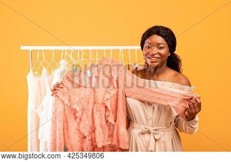 Professional Female Stylist Holding Fashionable Blouse Near Clothing Rack, Picking Elegant Outfit On
