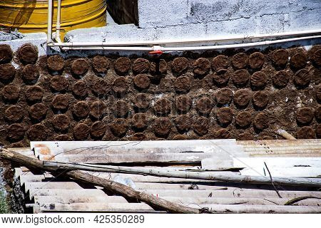 Stock Photo Of Cow Dung Cake Patties Drying On Wall Under Bright Sunlight At India Village Area, Pic