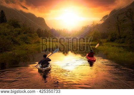 Adventure Friends Kayaking In Kayak Surrounded By Canadian Mountain Landscape. Dramatic Sunset Art R