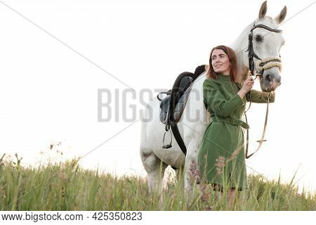 Young Attractive Woman In A Dress Is Walking With Her Horse, Holding Her By The Bridle, In A Meadow,