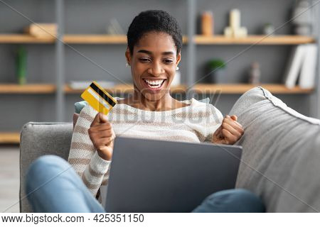 Online Banking. Cheerful Black Woman With Laptop And Credit Card At Home