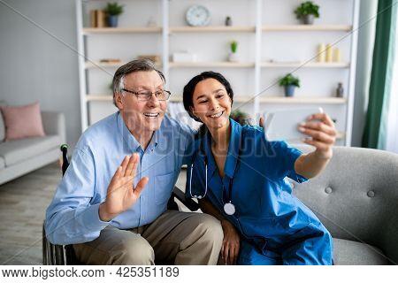 Young Medical Worker And Her Older Handicapped Patient Taking Selfie Together Indoors. Home Care Ser