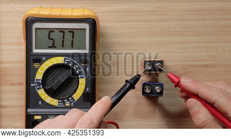 Testing 9v battery cell with digital multimeter tool, voltage check showing low volatage, batty depleted, discharged