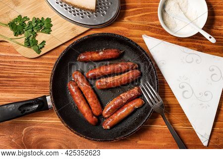 Tasty Fried Sausages In Frying Pan With Parmigiano And Parsley, Over Wooden Background. Top View