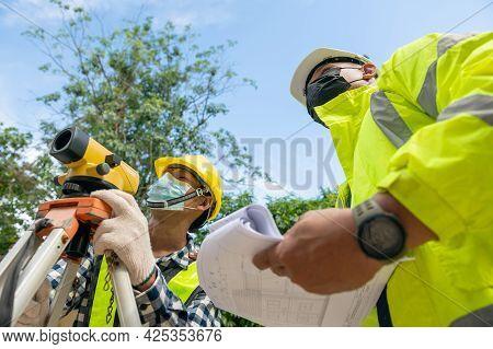 Surveyor Team Civil Engineer Working With Surveyor Telescope Equipment Making Contour Plan For Const
