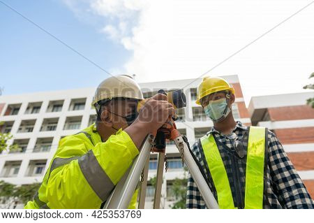 Team Engineer Surveyor With Telescope Equipment Surveying Work Building Inspection.