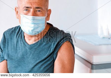 Senior Man Wearing Protective Mask Getting Ready For Injection. Senior Man In Clinic, Hospital. Elde