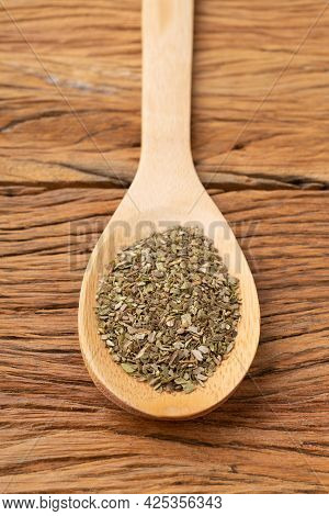 Closeup Of Dried Oregano On A Spoon Over Wooden Table.