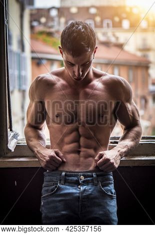 Sexy Shirtless Muscular Young Man Next To Window, Wearing Only Jeans, Looking Out