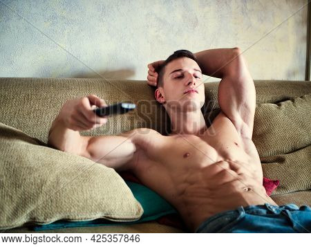 Bored Muscular Young Man Watching Tv With Remote Control