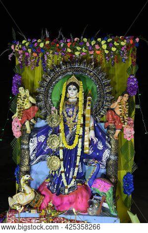 Idol Of Goddess Saraswati Being Worshipped, At Night. Colorful Light On Hindu Goddess. Howrah, West