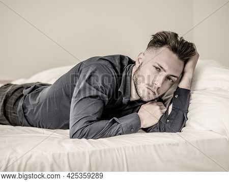 Sexy Young Man On Bed With Blue Shirt