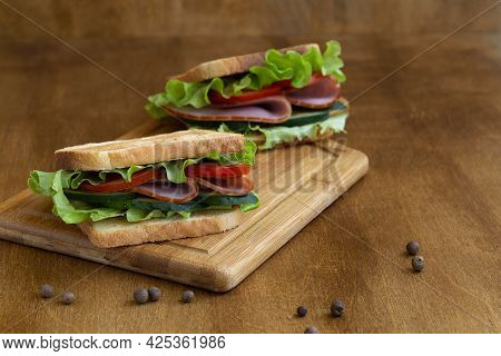 Sandwich With Salami.two Tasty Sandwiches With Ham, Green Salad, Cucumbers And Tomatoes On The Woode