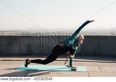 Young healthy sportswoman with prosthetic leg exercising on a fitness mat outdoors wearing headphone
