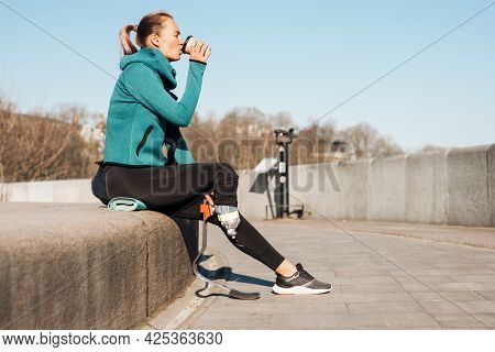 Young healthy sportswoman with prosthetic leg resting sitting outdoors drinking water from a bottle