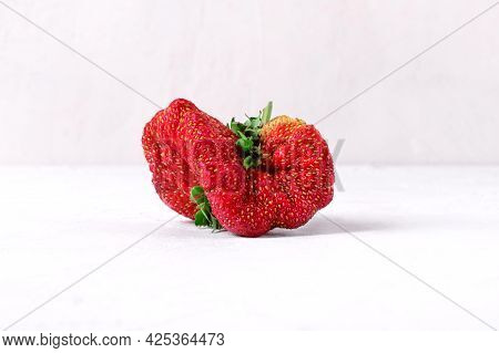 Weird Looking Strawberry. Imperfect But Tasty Farmer Product On White Table. Fighting Food Waste