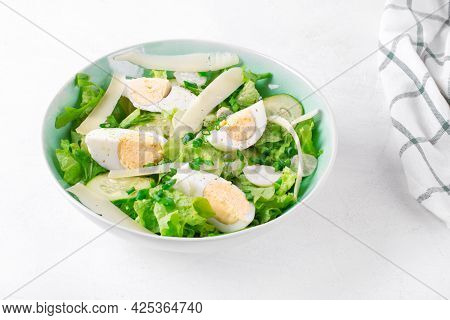 Salad With Eggs, Lettuce, Cheese, Cucumber, White Radish And Scallion Served In The Bowl On The Whit