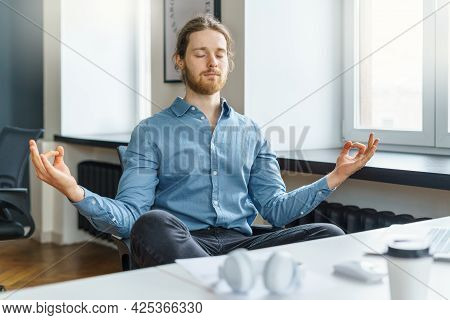 Taking Break. Calm And Peaceful Young Businessman With Closed Eyes Meditating And Relaxing During Ha