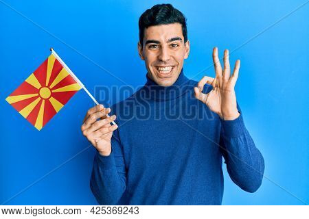 Handsome hispanic man holding macedonian flag doing ok sign with fingers, smiling friendly gesturing excellent symbol