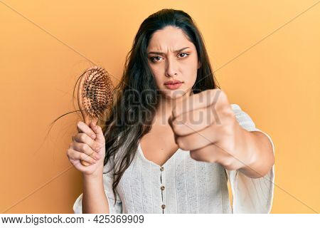 Beautiful middle eastern woman holding comb loosing hair annoyed and frustrated shouting with anger, yelling crazy with anger and hand raised