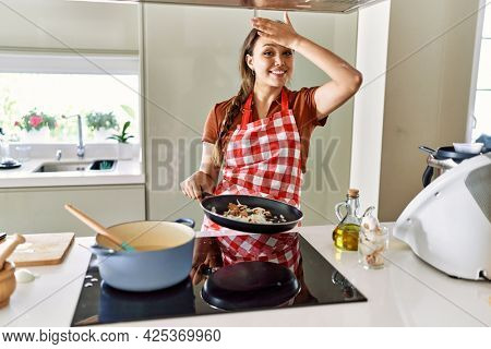 Beautiful young brunette woman wearing apron cooking at the kitchen stressed and frustrated with hand on head, surprised and angry face