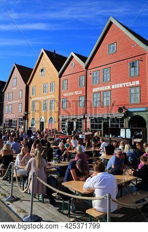 Bergen, Norway - July 23, 2020: People Visit Sidewalk Cafe In Bryggen District Of Bergen, Norway. It