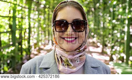 Close-up Of A Woman In A Headscarf And Sunglasses Smiling In A Garden Arch.
