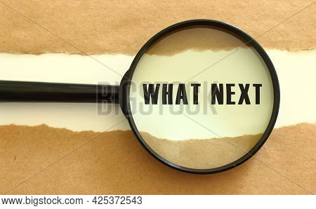 The Magnifying Glass Reveals The What Next Text Appearing Behind The Torn Brown Paper. Business Conc