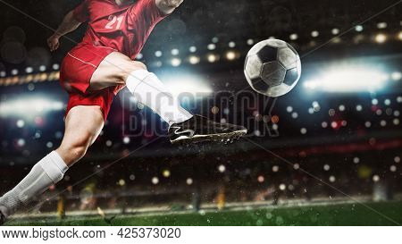 Close Up Of A Soccer Scene At Night Match With Player In A Red Uniform Kicking The Ball With Power