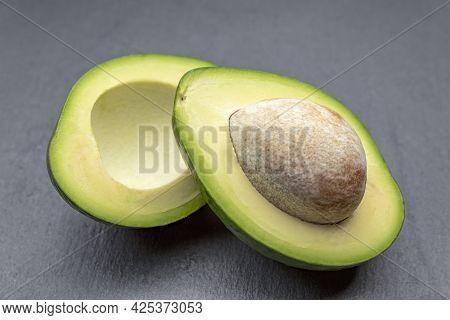 Fresh Avocado Cut In Half. An Avocado With A Bone Lies On A Black Stone Tray. Healthy Food Concept.