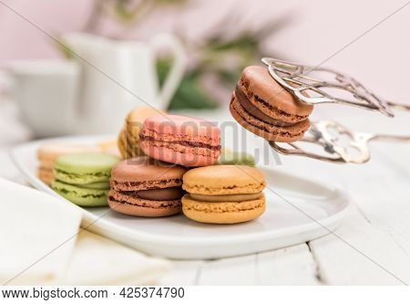 Assortment of French macarons pastry on coffee table, focus on a chocolate flavored one held up with pastry tongs