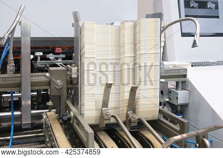 Elements Of Corton Boxes Are Collected In Stack. Conveyor Line For The Production Of Boxes. Machine