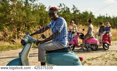 Happy Young African American Boy Resting On Retro Scooter Outdoors In Warm Sunny Day With Company Of