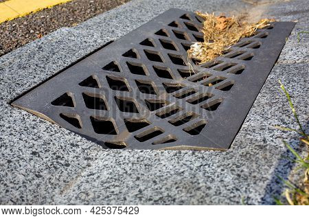 Grate With Holes For Drainage Of Storm Water From A Concrete Ditch On The Side Of An Asphalt Road Cl