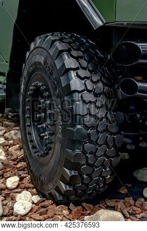 Wheel Of An Armored Car. Close-up Of A Large Off-road Armored Car Tire On Display At The Internation