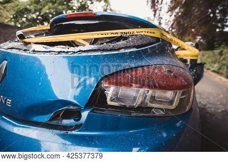 London | Uk - 2021.06.12: An Abandoned, Stolen Burnt Out Blue Car Parked On The Sideway Parking Spot
