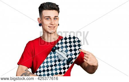 Young caucasian boy with ears dilation holding skate smiling happy pointing with hand and finger