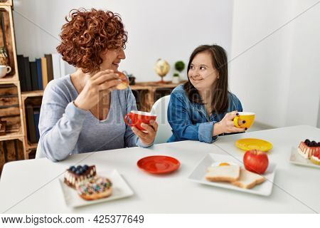 Mature mother and down syndrome daughter having coffee and lunch at home