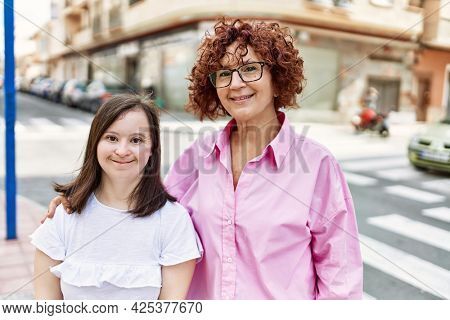 Mature mother and down syndorme daughter smiling happy and friendly outdoors