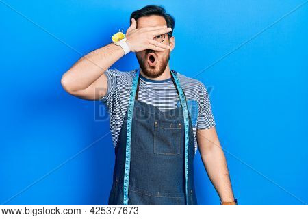 Handsome caucasian man with beard dressmaker designer wearing atelier apron peeking in shock covering face and eyes with hand, looking through fingers afraid