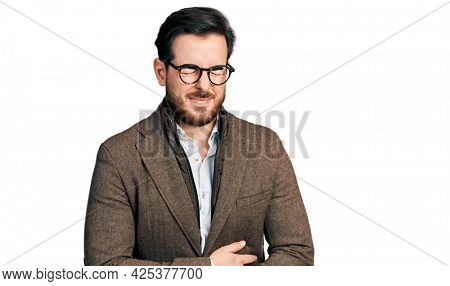 Young hispanic man wearing business jacket and glasses with hand on stomach because indigestion, painful illness feeling unwell. ache concept.