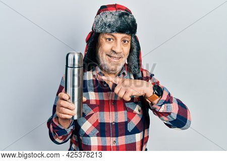 Handsome mature handyman wearing winter hat with ear flaps holding thermo smiling happy pointing with hand and finger