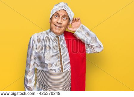 Senior hispanic man wearing tradition sherwani saree clothes smiling with hand over ear listening an hearing to rumor or gossip. deafness concept.