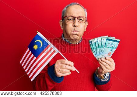 Handsome senior man with grey hair holding malaysia flag and malaysian ringgit banknotes puffing cheeks with funny face. mouth inflated with air, catching air.
