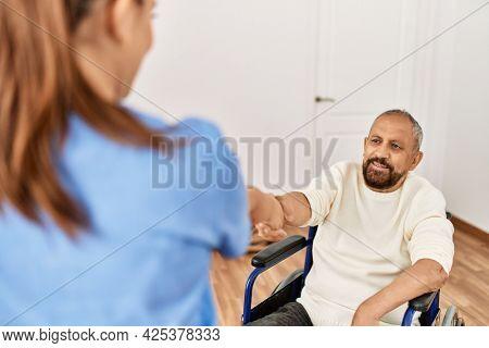 Senior man sitting on wheelchair  and geriatric nurse doing hand shake agreement, thanking for help